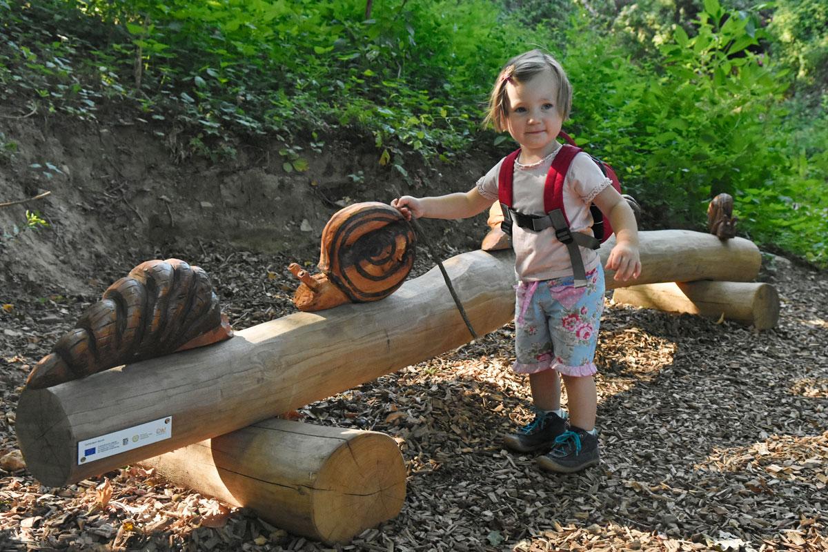 Kleines Mädchen Steht vor einem geschnitzten Baumstamm mit geschnitzter Schnecke.