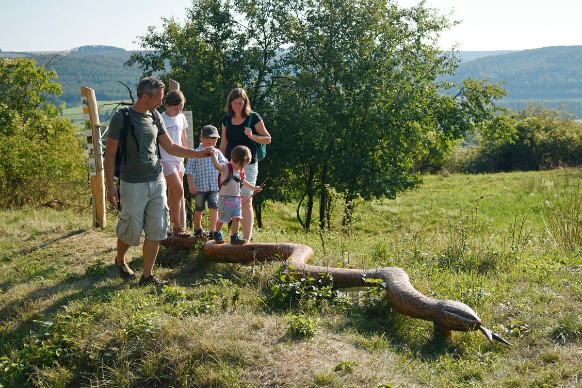 Kinder balancieren auf einer holgeschitzen Schlange, Eltern helfen ihnen