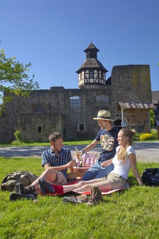 Drei junge Erwachsene picknicken in Wanderkleidung neben dem Wanderweg