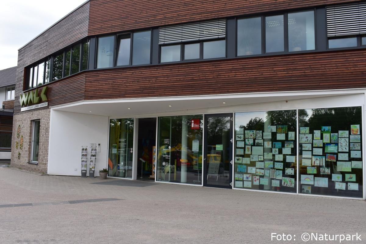 Foto des WALK Gebäude mit einer bunten Festerfront aus gemalten Bildern bei der Touristinformation