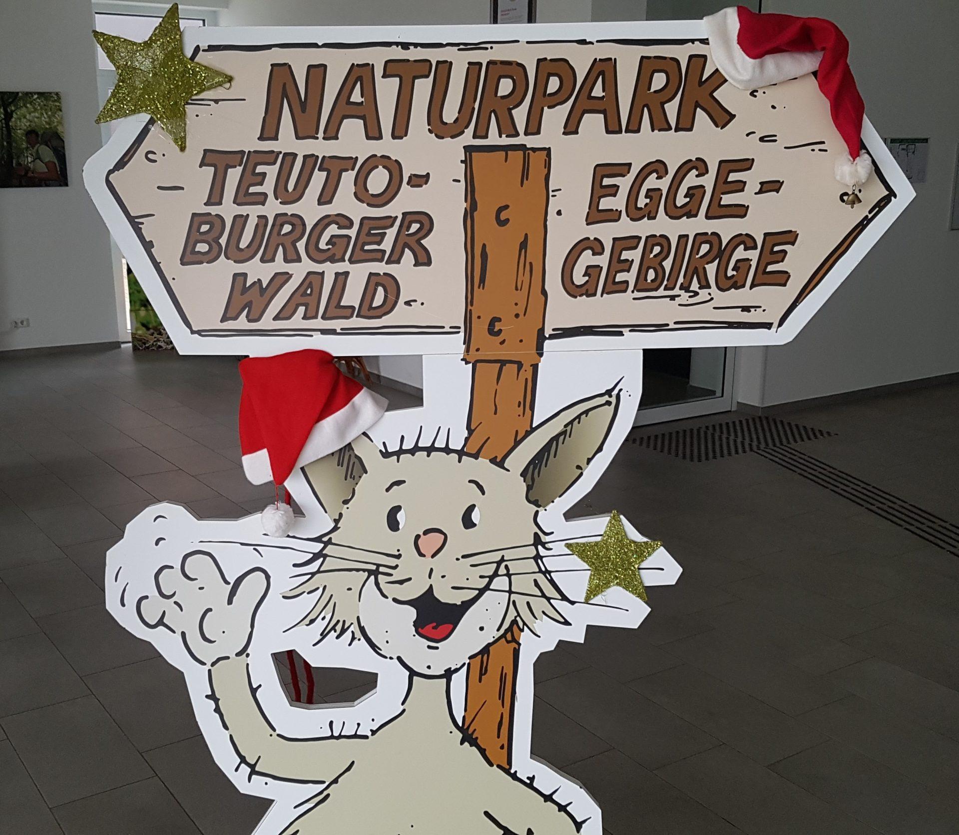 """Pappaufsteller der gezeichneten Wildkatze """"Teutus"""" winkend am Aufsteller Naturpark Teutoburgerwald/ Eggegebirge"""