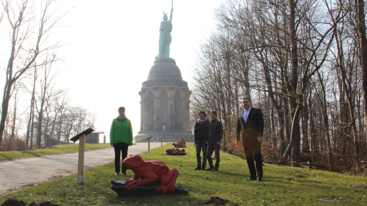 Rot geschnitzter Frosch und andere Tiere vor dem Hermannsdenkmal mit vier präsentierenden Leuten