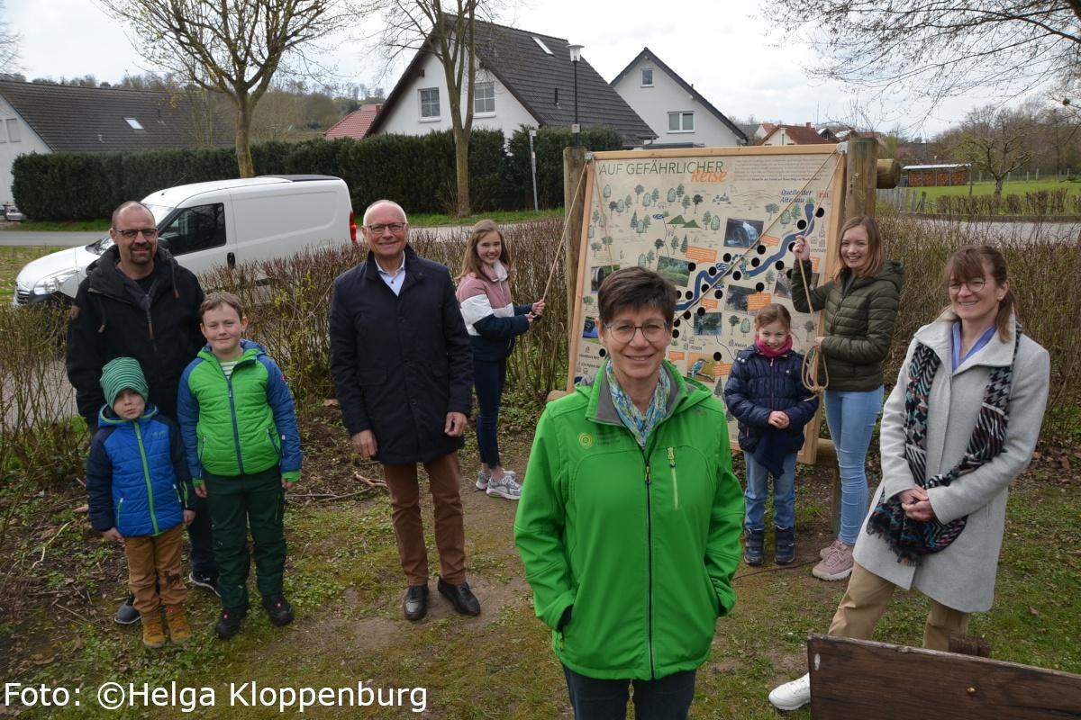 Die neuen Infoschilder an der lebendigen Altenau werden von Kindern und Erwachsenen aufgestellt.