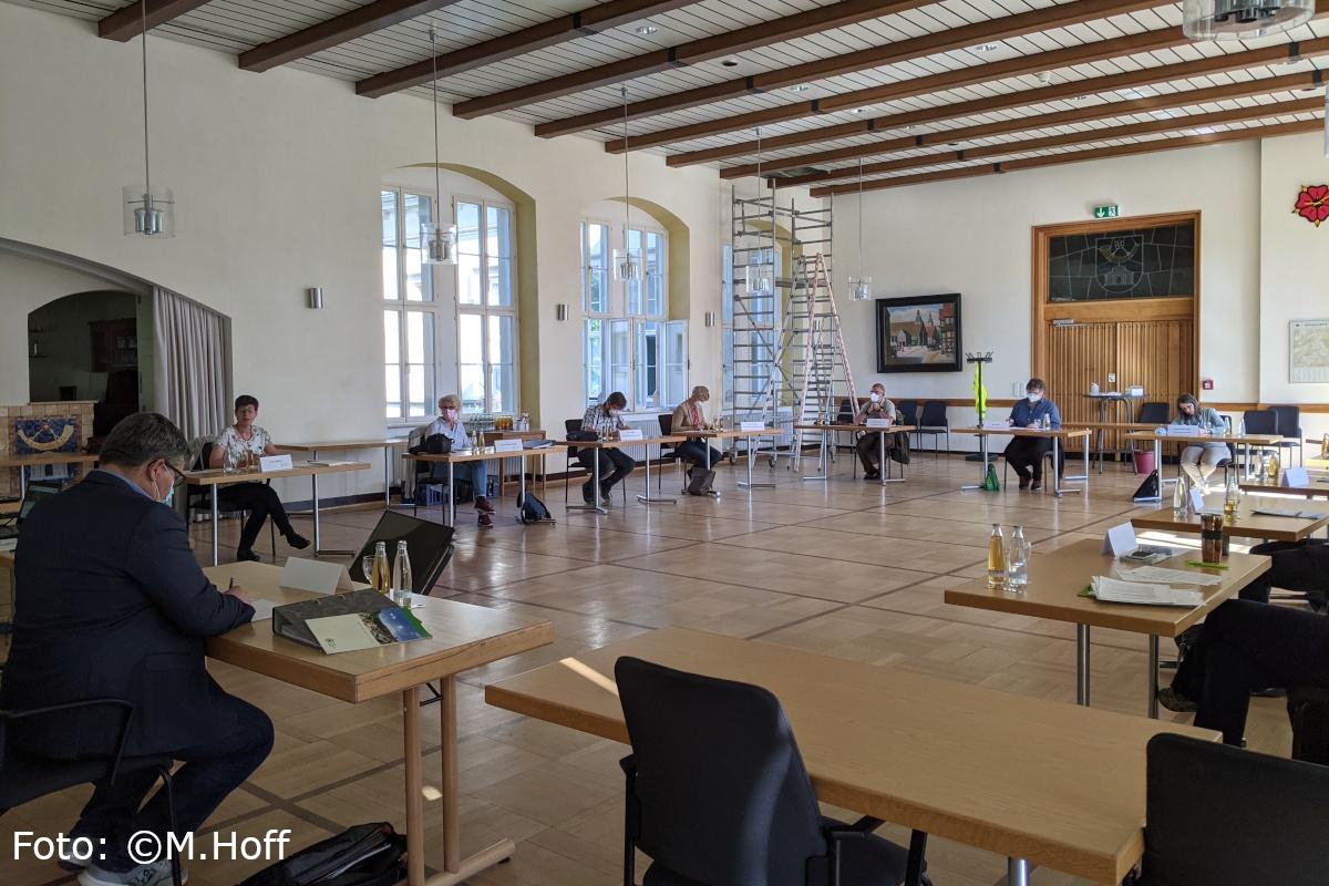 In einem großen Raum sitzen die sich Beratenden konzentriert an ihren Einzeltischen in einem Kreis.